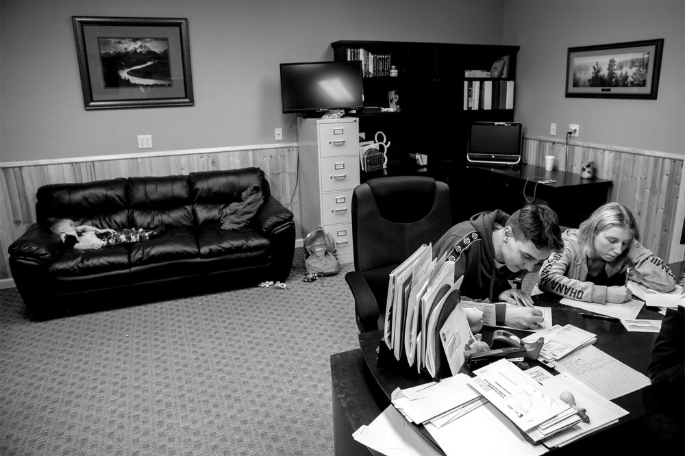 Sergey, 16, and Tanya, 15, write letters at Robert and Janelle Pfeil's workplace while Rayden Pfeil, 2, takes a nap on the couch. With the Pfeil's other kids at school during the day after the holiday breaks, the Ukraine orphans are left to entertain themselves through video games and other means while Robert and Janelle work.