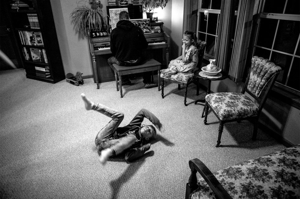 Natalia, 11, rolls backwards across the floor after an attempted sneak up on Derrick Mitchell on the piano, as Leila Pfeil, 9, looks on, during a family get-together on Wednesday, Jan. 9, 2019. Derrick and his wife are looking to adopt three kids, in addition to the six they already have.