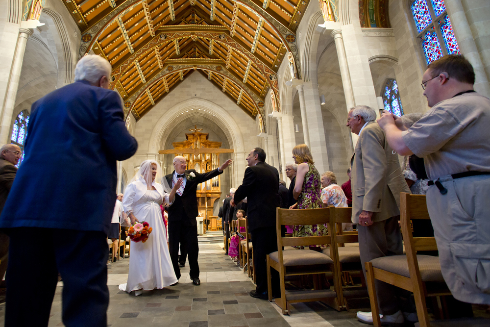Joyce and Frank wave to family and friends as they walk down the aisle as Mr. and Mrs. Maslyn at Sacred Heart Cathedral.