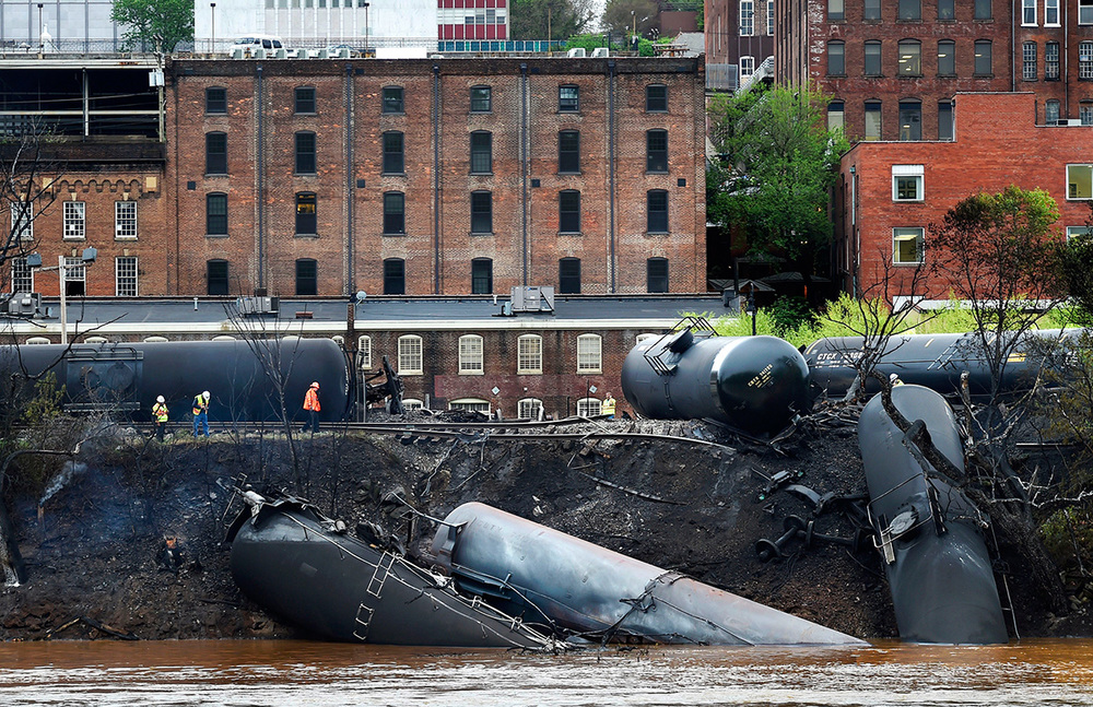 Firefighters and rescue personnel work along the tracks where several CSX tankers carrying crude oil derailed and caught fire, spilling 20,000-plus gallons of oil into the James River in Lynchburg, Va.