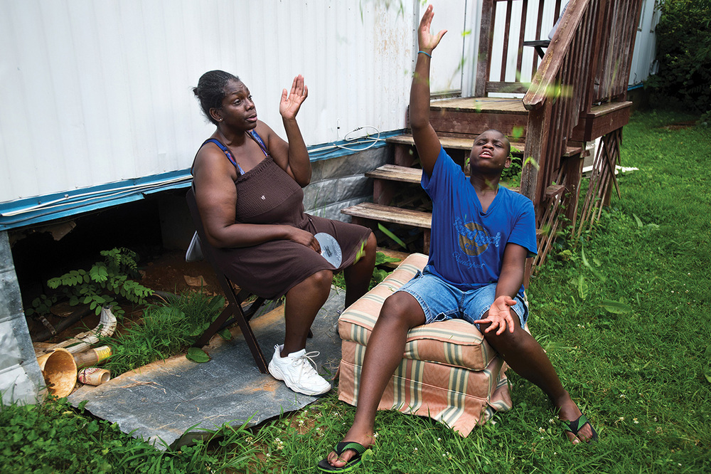 "Cortez tosses grass in the air while sitting in the yard with his mother. Ruby and her son spent the evening outdoors as temperatures rose above 90 degrees inside their home, after they lost their air conditioning because she couldn't afford to pay her bill. ""Cortez deserves better than this,"" said Ruby, who took the day off work to try to find assistance to pay her overdue electric bill."