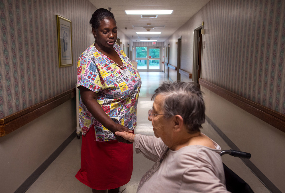 "Ruby shakes hands with a resident at The Carrington. ""I know we got to get paid to make ends meet,"" she said. ""But it's not all about money; it's about me going to work and taking care of them."""