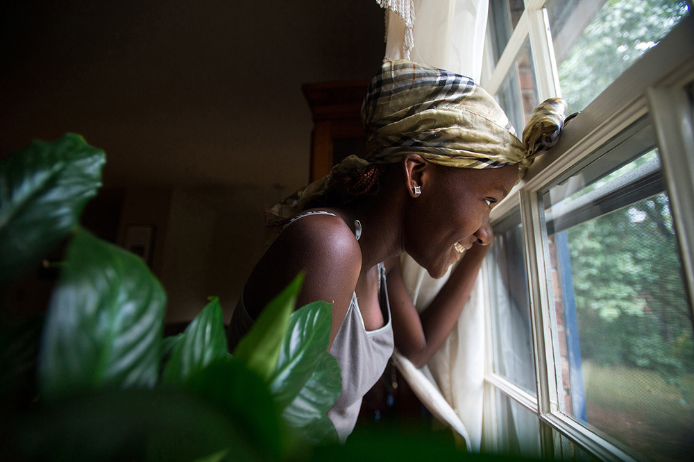 Promise Guy, 13, looks out the window at her friend, Sahara McKnight, 12, as she explores the outdoors after they arrived at their host family's home in Madison, Heights, Va.