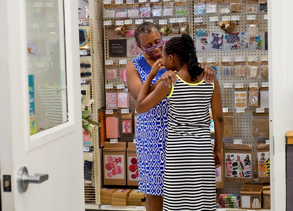 Barbara Austin comforts Sahara as she wipes away tears after frustrations from making rubber band jewelry led her to take a break from the class at Michaels.