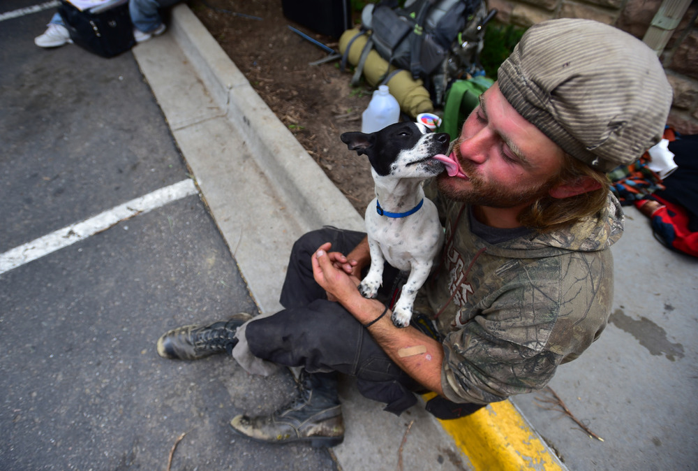 Barak Gills, a homeless man, kisses his dog Jack while waiting for lunch outside of the Carriage House in Boulder, Colo.