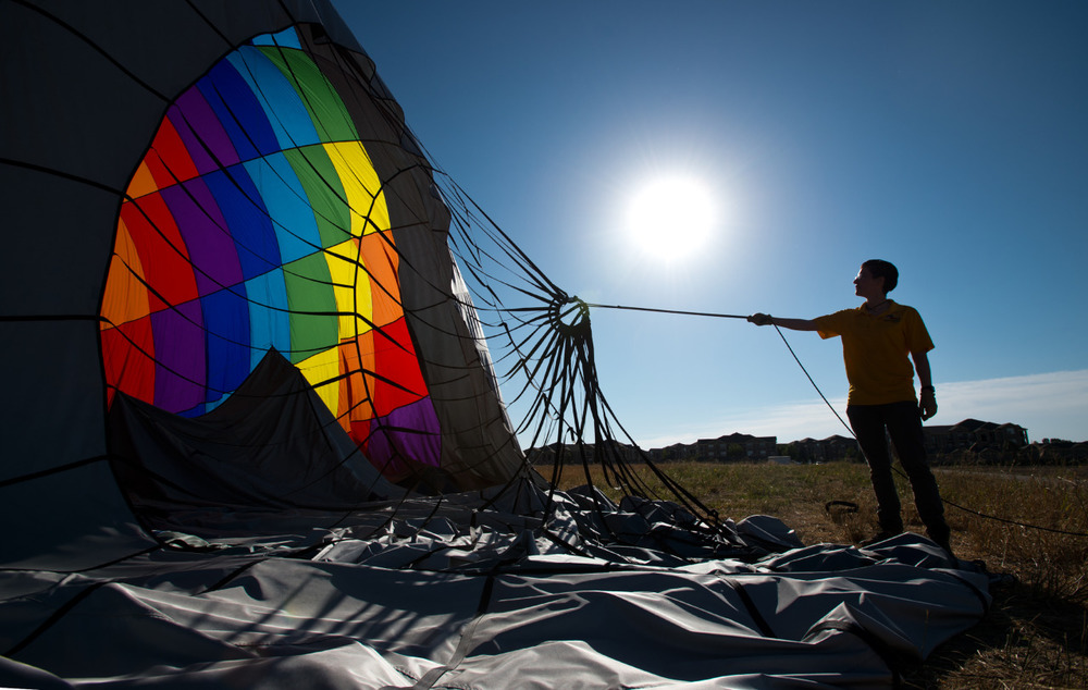 Christina Longman, a crew member with Fair Winds Hot Air Balloon Flights, helps take down an air balloon after a morning launch in Lafayette, Colo.
