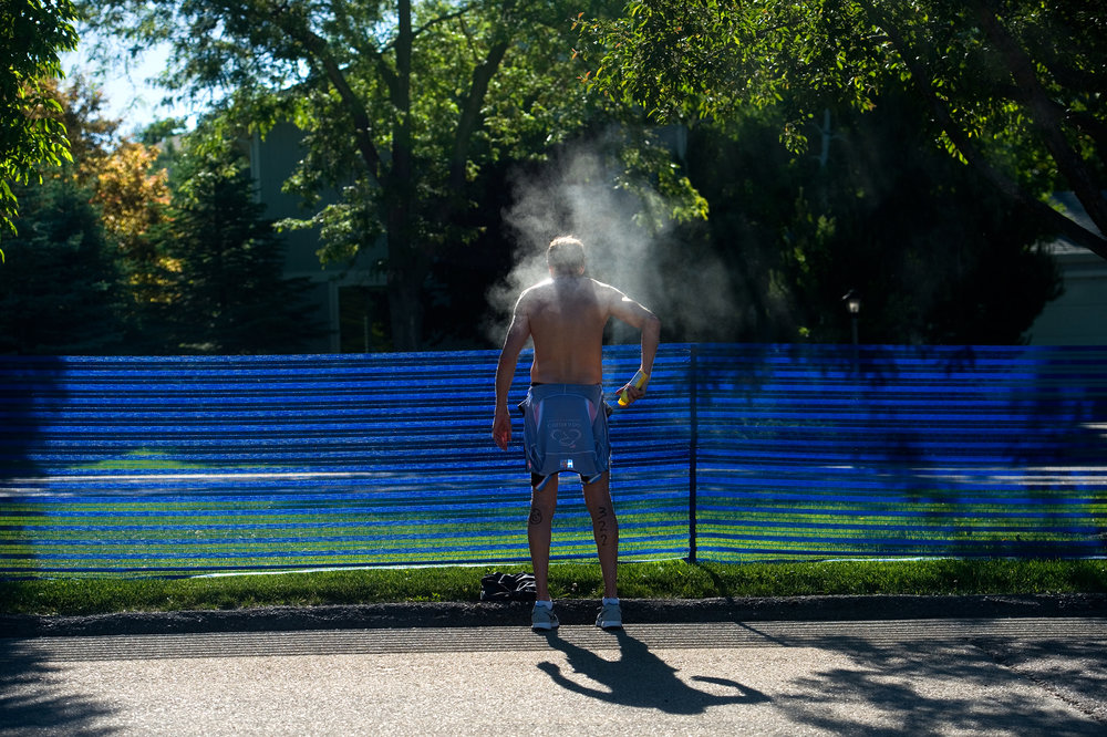 Thomas Beal sprays himself with sunscreen before beginning the biking portion of the Longmont Triathlon at Centennial Pool in Longmont, Colo.