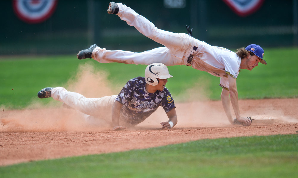 Boulder's Cooper Moore jumps over Albuquerque's Sal Ware as Ware slides into second base during the American Legion Western Regional Tournament at Scott Carpenter Park in Boulder, Colo.