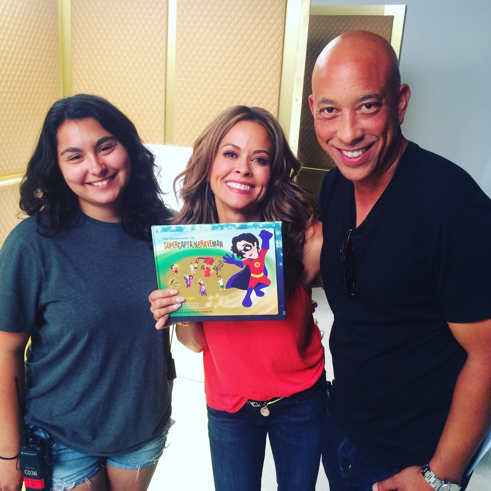 Brooke burke proudly displays her copy of supercaptainbraveman, accompanied by honour norman and co-author paul norman