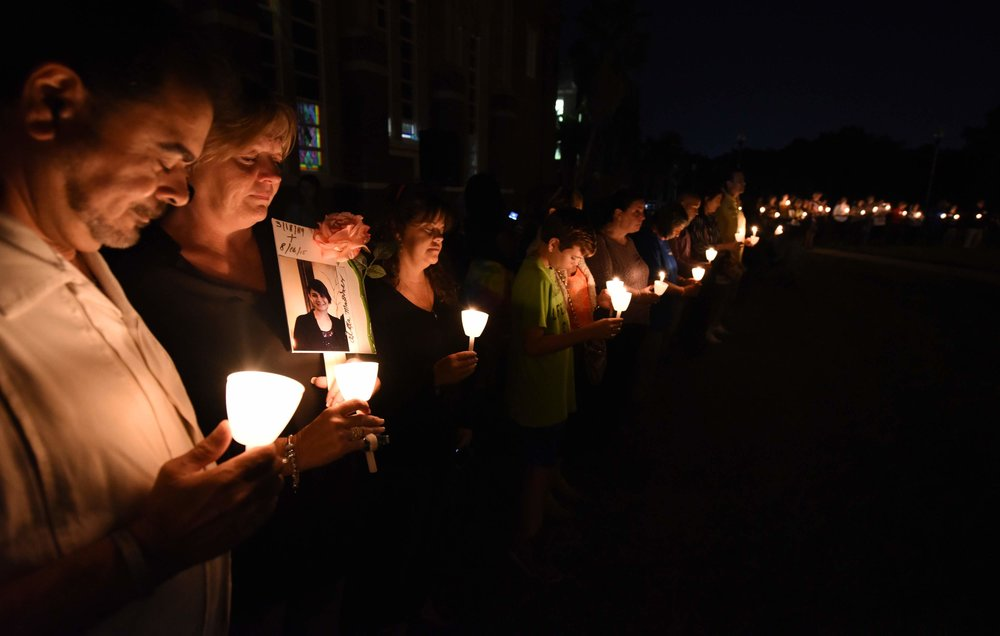 Heads are bowed for prayer during the NOPE Candle Light Vigil Thursday night at Hillsborough High School. JASON BEHNKEN / STAFF