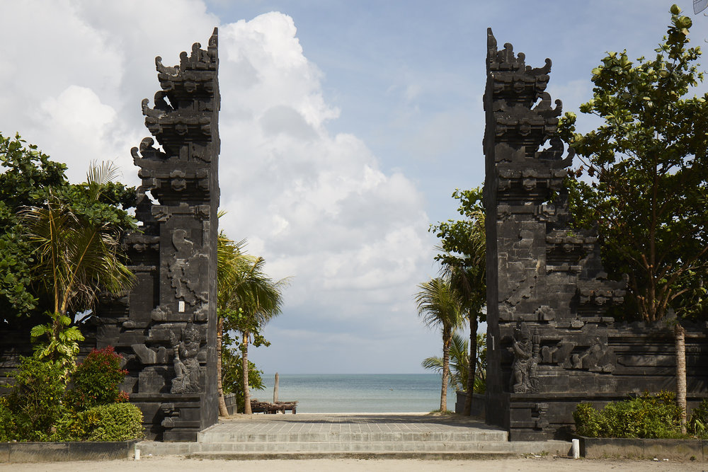 "View from my Motorbike at Jimbaran Beach, Bali, Indonesia.  I was told by a Balinese Hindu ""HolyMan' this type of gate represents a holy place, on top of the mountain.  You have the appearance of walking over the top and seeing the view below.  Being on top of everything (the world...spiritually)."