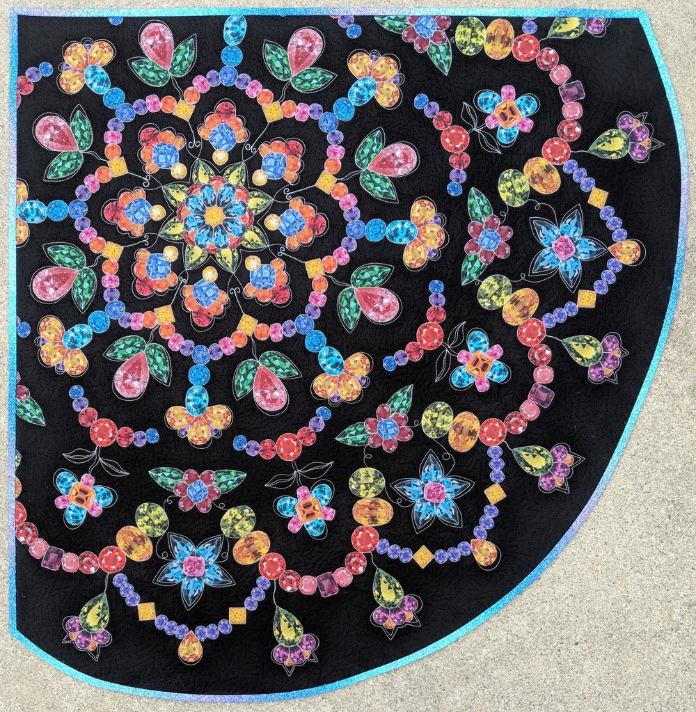 """12. Sparkling Stained Glass Mandala  June 2018 32"""" x 33"""" Made for the Hoffman Fabric Challenge. Challenge fabric featured jewels which were fussy cut out and laid out into a floral mosaic mandala design.  Exhibits/Awards: Chosen at Hoffman's Curator Choice for the Applique Category and is included in the Hoffman traveling exhibit (August 2018).   Blog Post"""
