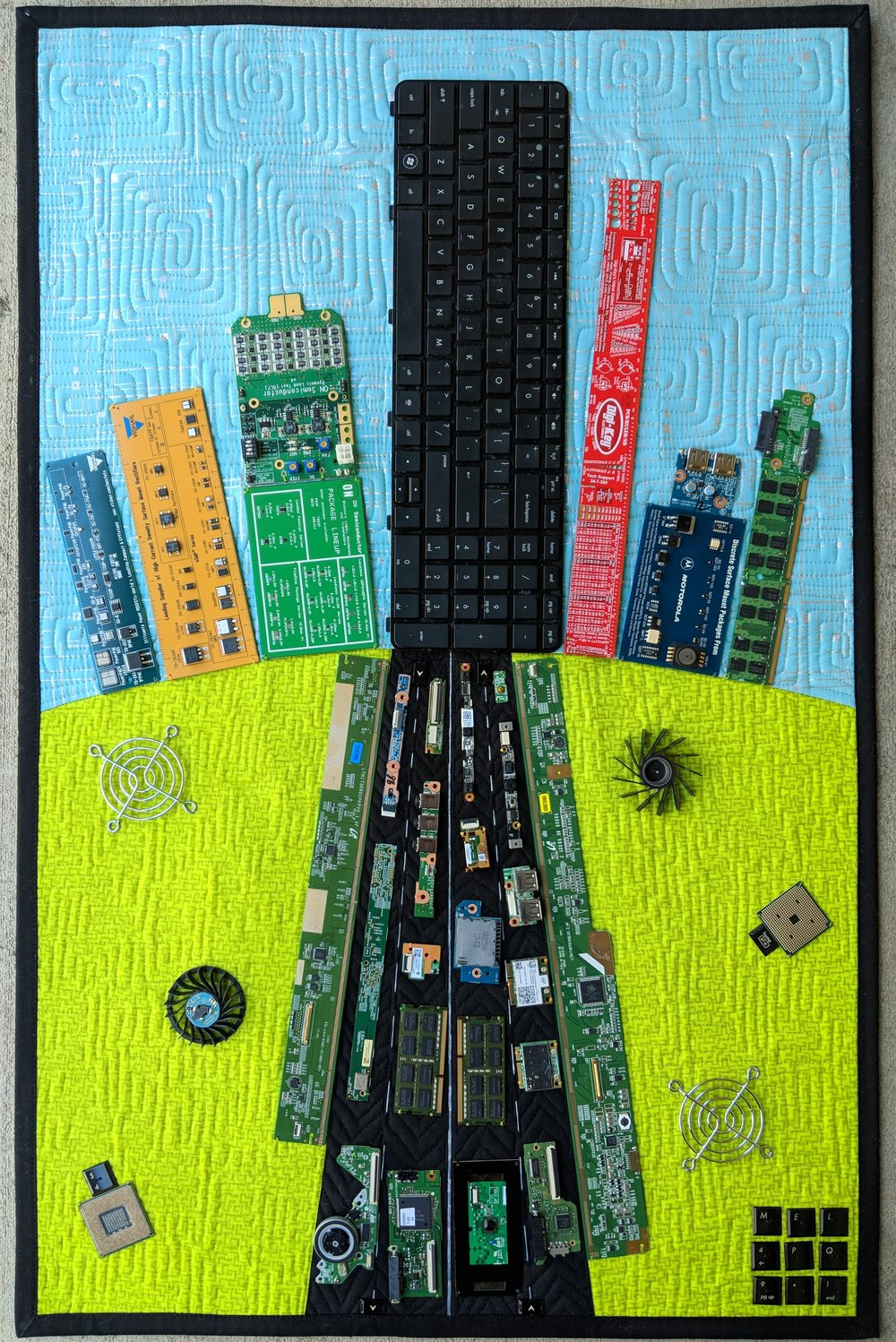 """1. Do You Know the Way to San Jose?  January 2018 22"""" x 34"""" San Jose/Silicon Valley is home to a growing number of high-tech companies, causing a major shift in the area's demographics, housing market, traffic, and local art scene. This abstract cityscape reflects the confluence of both industries: hardware as symbolized by the two upcycled HP laptops (note that HP was founded in Silicon Valley) and software, as represented in the printed fabrics and free-motion quilting in the background. The skyscrapers are indicative of the changing housing landscape towards more and more high-density apartments, several of which have been constructed near the San Jose Museum of Quilts & Textiles. The congested highway represents the swell in population, which has overwhelmed the current infrastructure, and has generated a mass exodus of families, working professionals, and artists who can no longer afford to live, work or create here in the Bay area.  Exhibits/Awards: Pacific International Quilt Festival (October 2018), won Viewer's Choice in Project Quilting's Hometown Proud weekly challenge (January 2018).   Blog Post"""