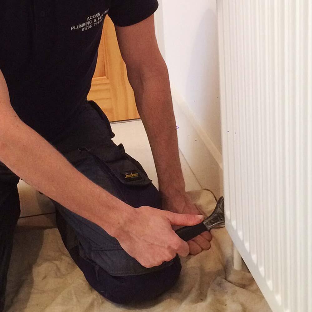 Man in Acorn uniform fixing heating radiator