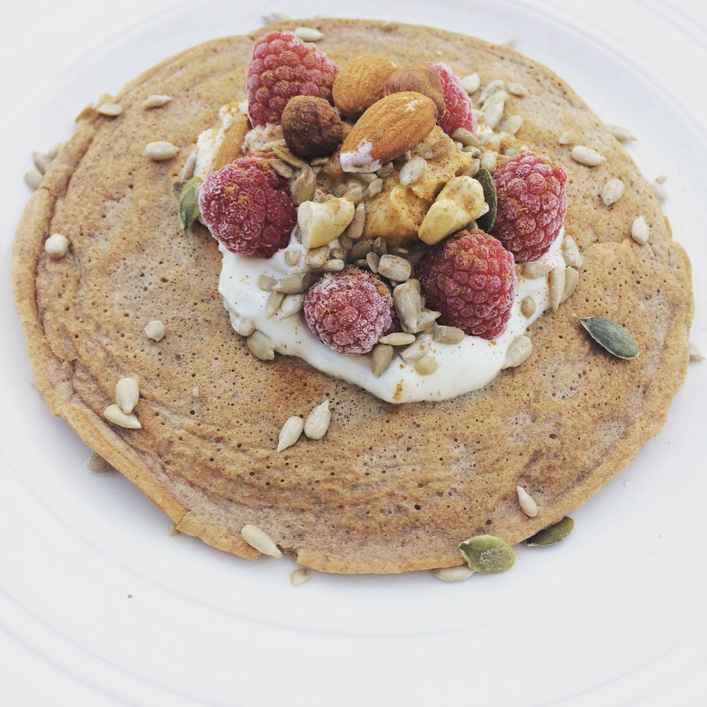 Pancake topped with greek yogurt, raspberries and nuts