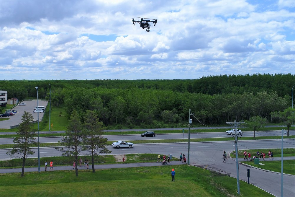 DJI Inspire 1 hovers safely over 100ft from any passers-by during the 2017 Crohn's & Colitis Canada Gutsy Walk at the Canadian Mennonite University.  M3 Aerial Productions ground crew ensures a 100ft buffer between drone operations and the public.