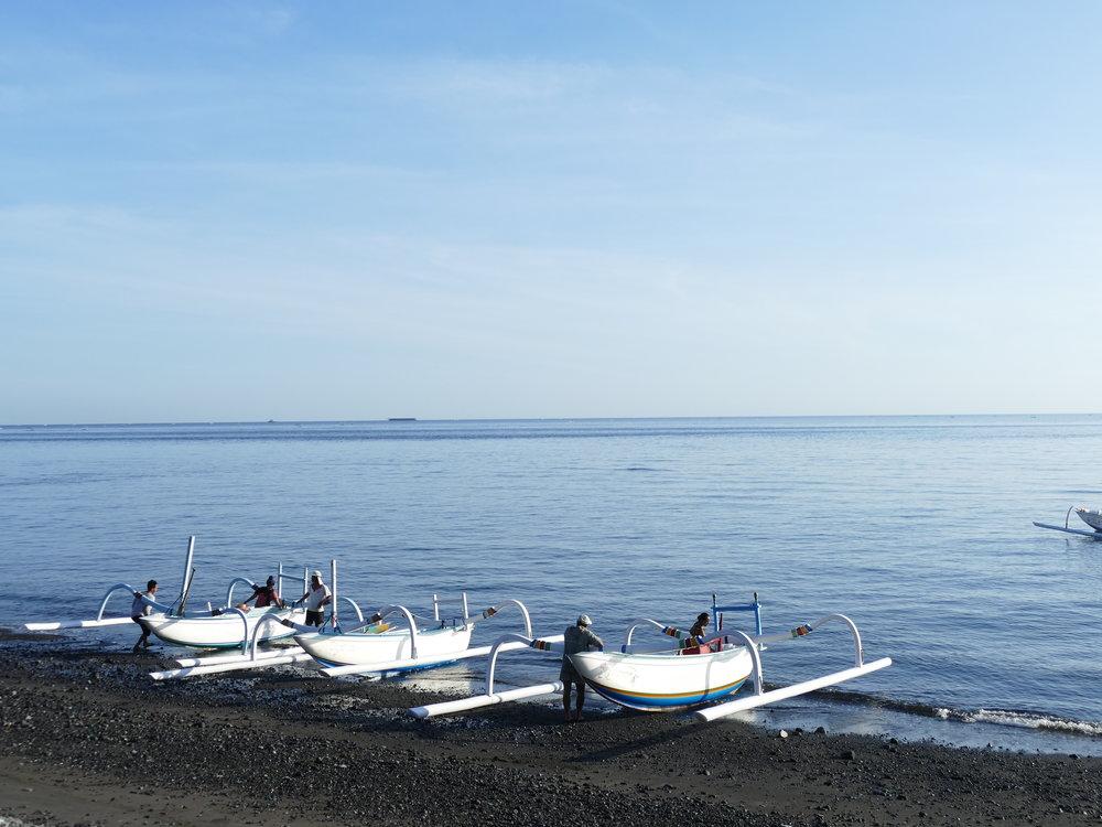 Les pêcheurs qui reviennent au petit matin avec les paniers remplis de poissons.