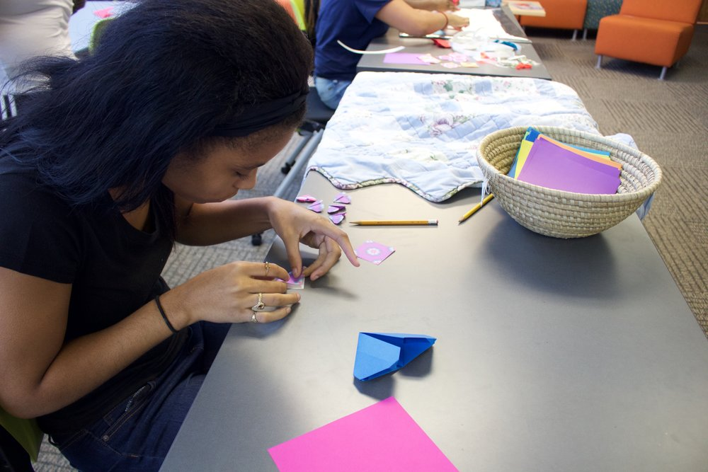 Family Care Center student making individual hearts for group project after origami and health lesson.