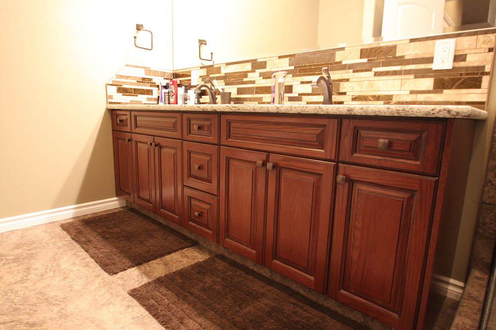 raised panel stained vanity with granite countertop
