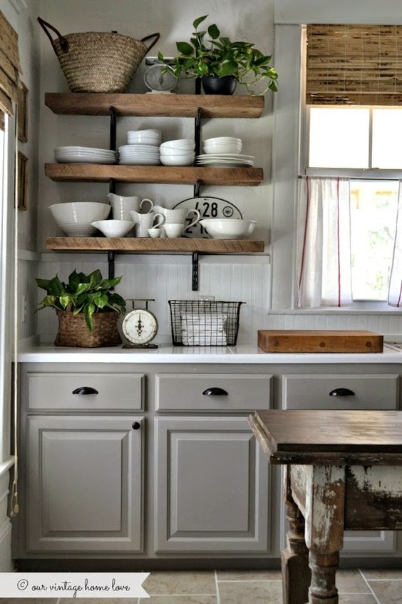 Rustic Shelving - Give your gray cabinets a boost of warmth with some rustic wood accents like these shelves. In order to tie the look together consider adding rustic decor and curtains.