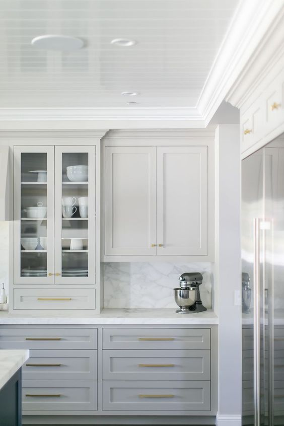 Multi-Hued Cabinets - Use different hues of the same color throughout your room. In this kitchen, the upper cabinets are painted the same color as the wall to give the built-in look a classy feel. The base cabinets are slightly darker and the island is dramatically darker/.