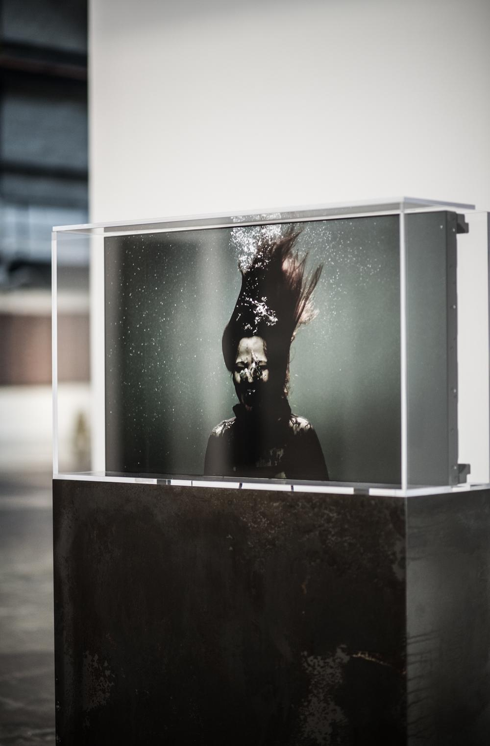 y2o Huis clos , 2015   Un mot de l'artiste  Prenant place dans une cuve, Huis clos est une adaptation de l'œuvre y2o. Dans ce vidéo d'une durée approximative de trois heures, le temps à été transformé et la trame narrative disparait pour faire place à la décomposition du mouvement des corps. Sept fois plus lente que y2o, cette œuvre questionne l'élasticité du temps et notre perspective sur cette dernière. Suspendus à l'extérieur de la réalité, les spectateurs sont invités à se perdre dans les émotions, gestes, et micromouvements à l'écran.