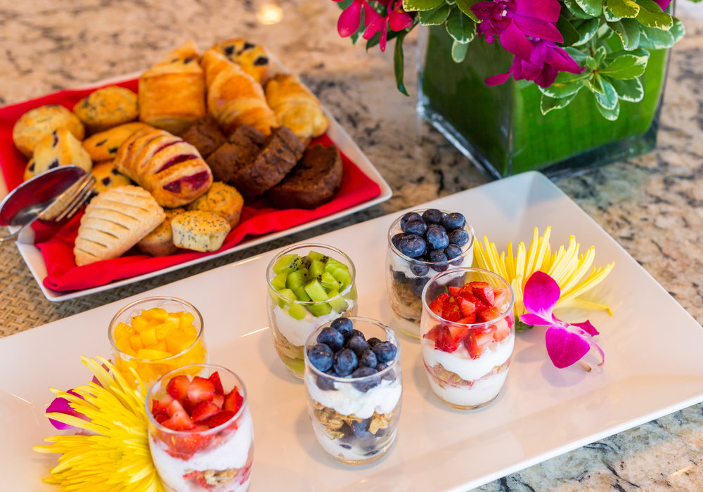 Breakfast french pastries and tropical fruits, oatmeal and greek yogurt parfaits.