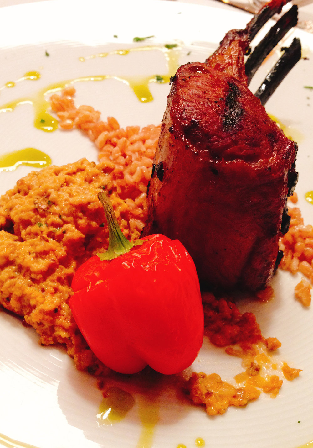 Marinated grilled rack of lamb with baba ganoush, feta sauteed peppers and orange farro.