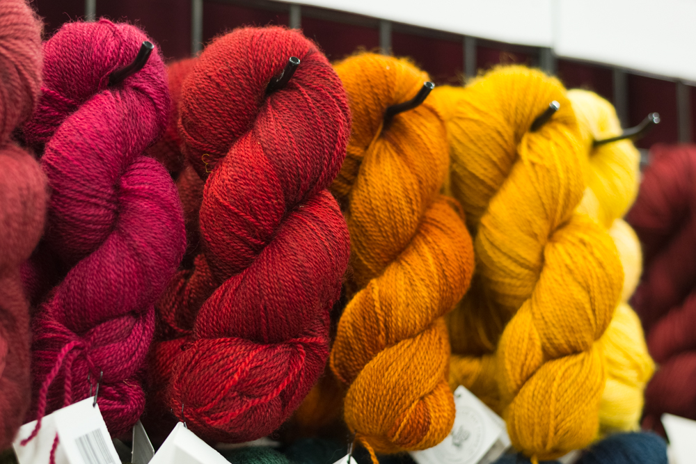 The Hollyberry is third from the left.  This is where I blame the arena lighting because this photo does not capture the perfect orange-tinged redness of this yarn