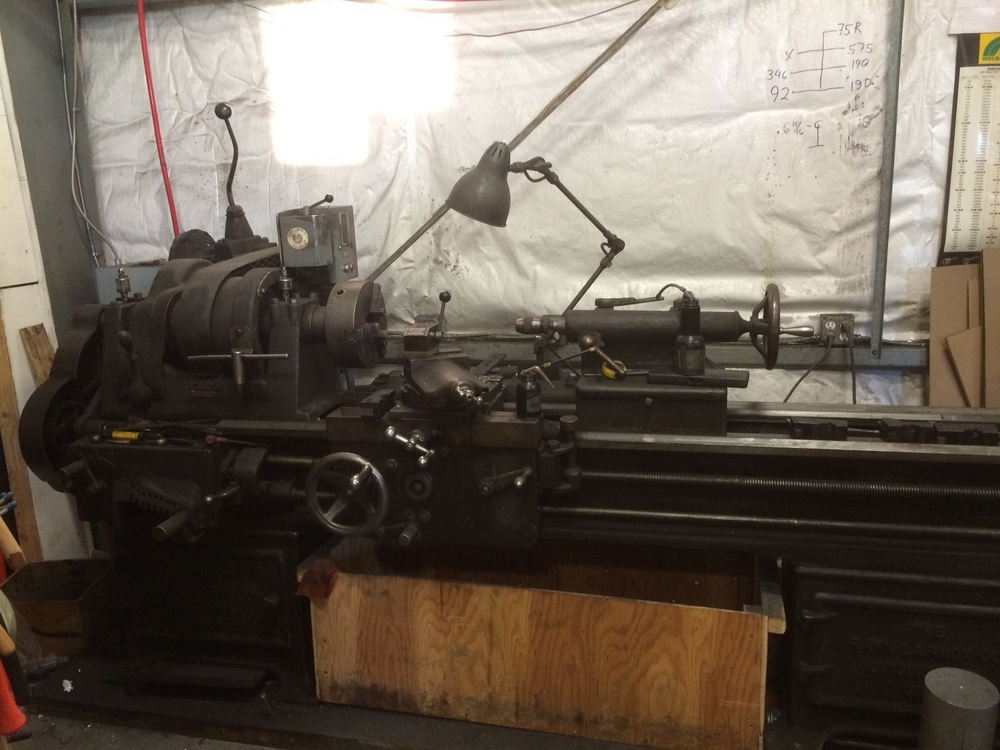 This lathe is a classic. Made by Rahn Larmon sometime between 1911 and 1941. It used to be powered by a flat overhead belt but someone along the line added an electric motor and 3 speed transmission from a truck for variable speeds. you can see the stick shift in the upper left corner. It was previously owned by Wards Cove Packing, a seafood processor and before that by Libby McNeil Libby, which is still around as Libby's which processes canned fruit.