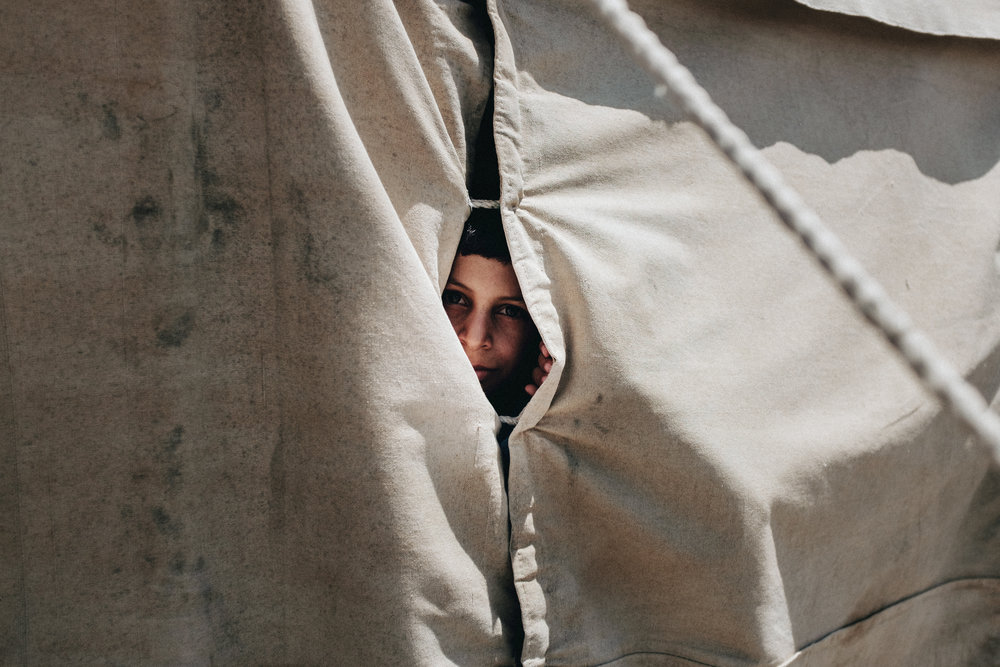 A young boy peers out of a gap in his tent in the Bartalla IDP camp, Iraq.