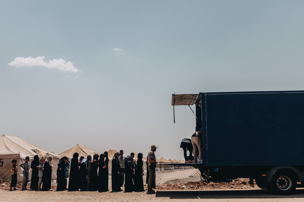 Residents of the camp stand in line and wait to recieve basic supplies such as tooth brushes, nappies and baby formula from the back of a truck operated by the One World Medical Mission.