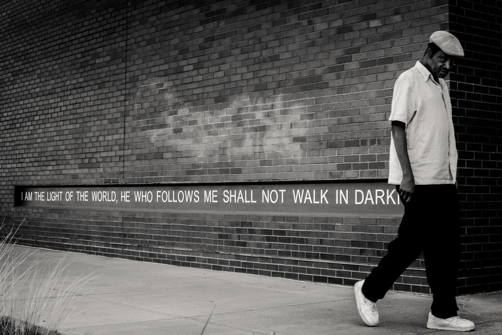 A man walks by a quote from Jesus. The Hills is committed to shining Jesus light in our Denver neighborhood.