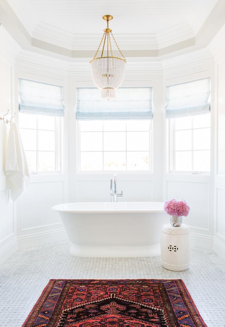 Marble+basketweave+tile,+Persian+Rug+in+the+bathroom+and+chandelier+over+tub+--+Studio+McGee.jpg
