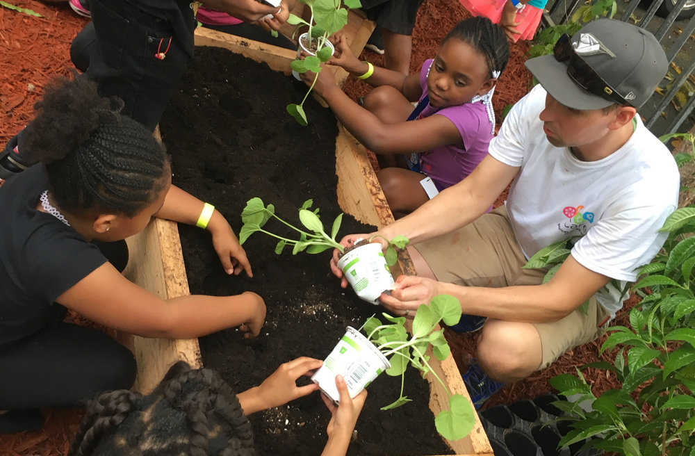An Avolon employee volunteer teaches children how to plant vegetables in a newly built garden box at the Nan Knox Unit Boys & Girls Club of Broward County in Fort Lauderdale, Florida. This activity was part of their annual Care Day.