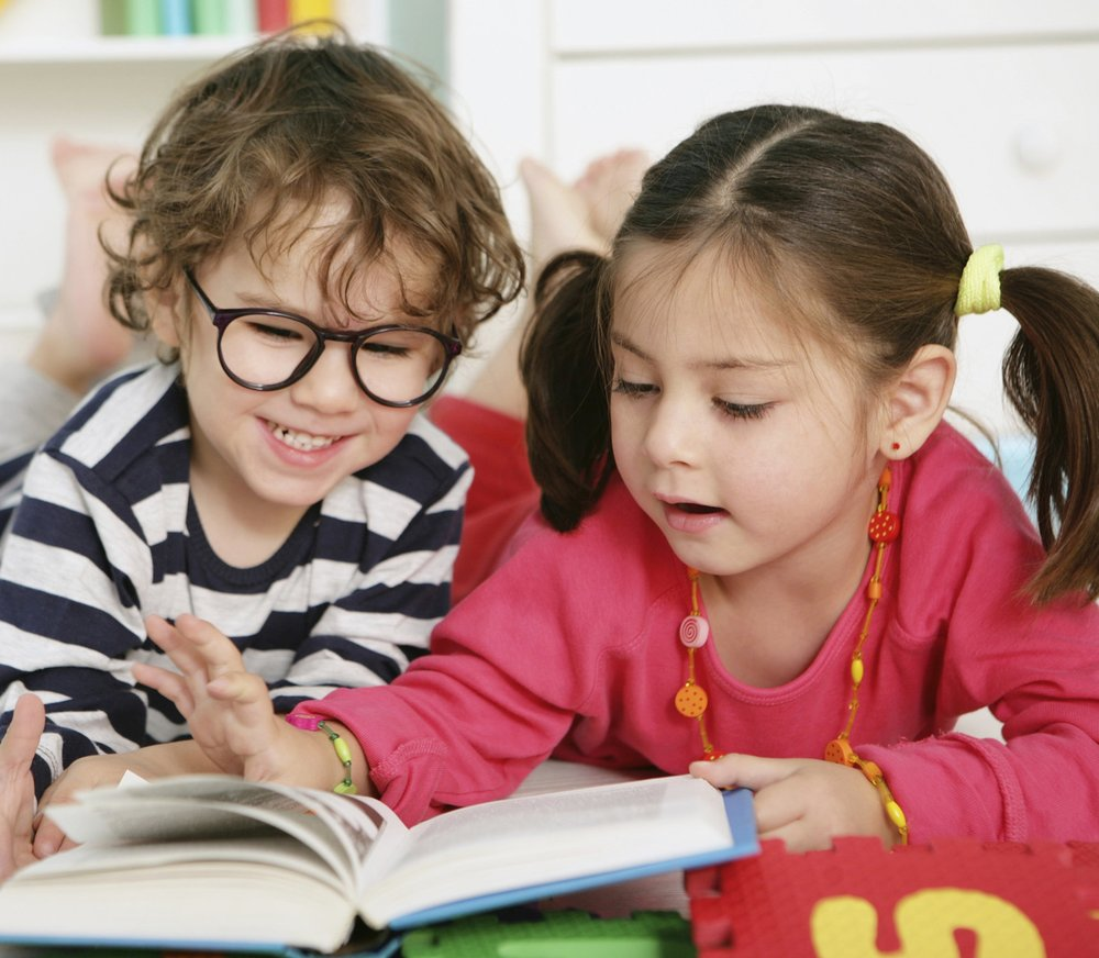 """Toddler boy and girl reading. Links to """"Where We Are"""" page."""