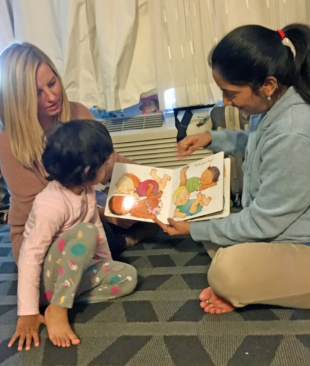 Katherine Quinn (left) a parent educator with the Springfield Parents as Teachers program, assists a family with early childhood educational development during a home visit in Greene County.