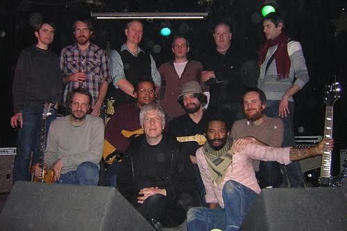 Empty Bottle G3 all stars! (Empty Bottle, Chicago, 2007) left to right (standing): Tim Iseler, David Daniell, Tod Rittman, John McEntire, Doug McCombs, Adam Vida; (left to right kneeling): Eric Block, Jeff Parker, Josh Abrams, Benjamin Vida; (in front): Rhys and Robert Lowe.   Courtesy of Rhys Chatham.