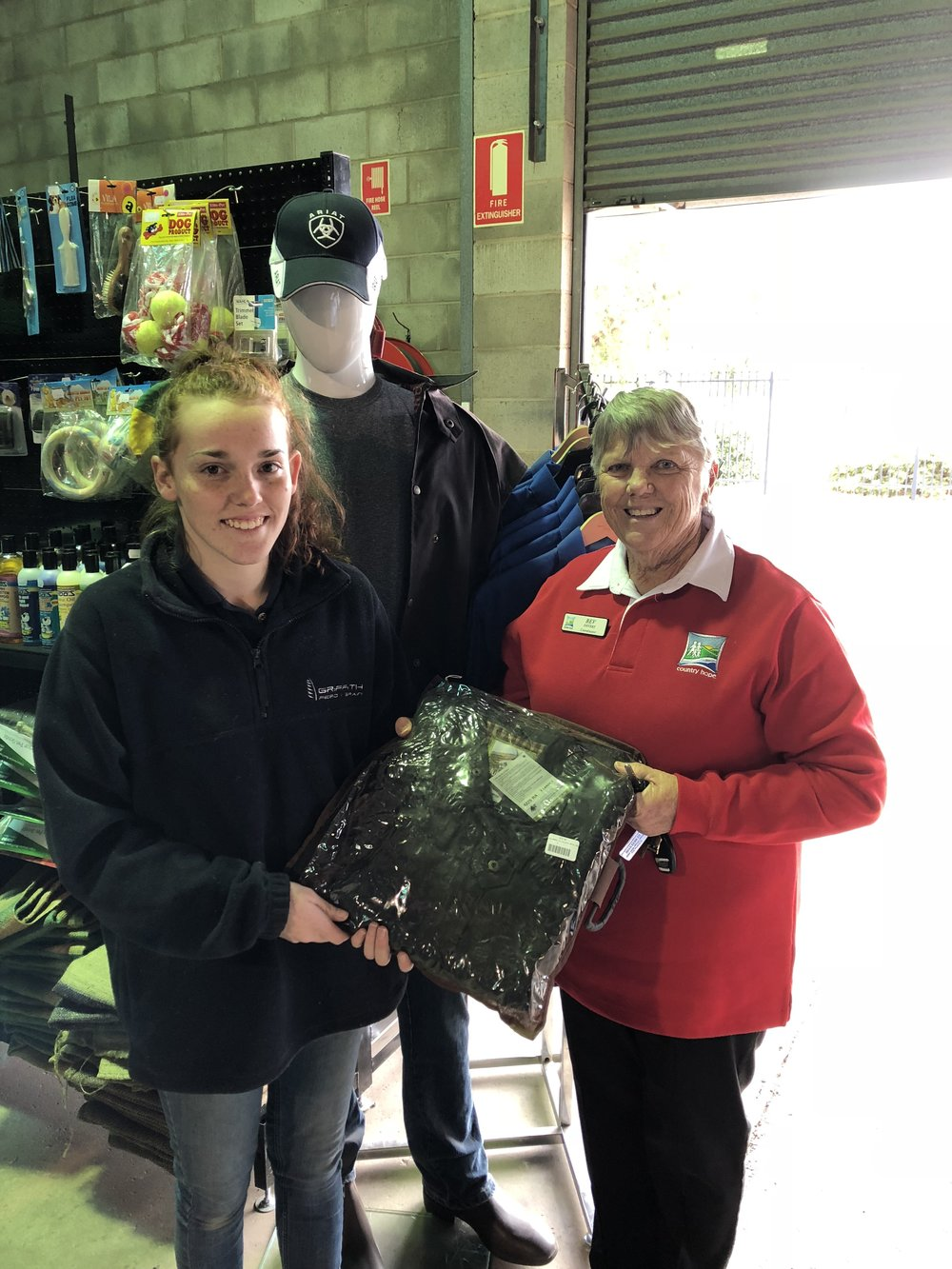 Joedee from Griffith Grain & Feed and Bev.  Joedee from Griffith Grain & Feed handing over the Nullarbor Coat for the raffle at the Murrumbidgee Country Music Festival, Griffith Fundraising Group thanks them for a very generous donation.