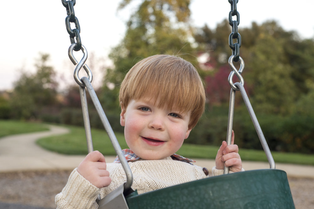 Caitlyn Lunsford is a Lifestyle Photographer. This photo is of a boy in a swing at the park.
