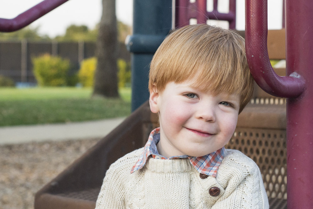 Photograph of a two year old boy sitting on the steps at a playground by Caitlyn Lunsford, a Lifestyle Photographer
