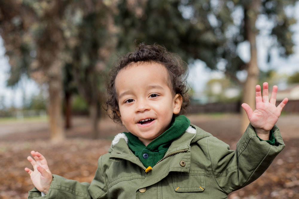 Caitlyn Lunsford Photography - Why You Should Take Holiday Photos Before Thanksgiving. This is a photo of a boy at a park wearing a dark green jacket.