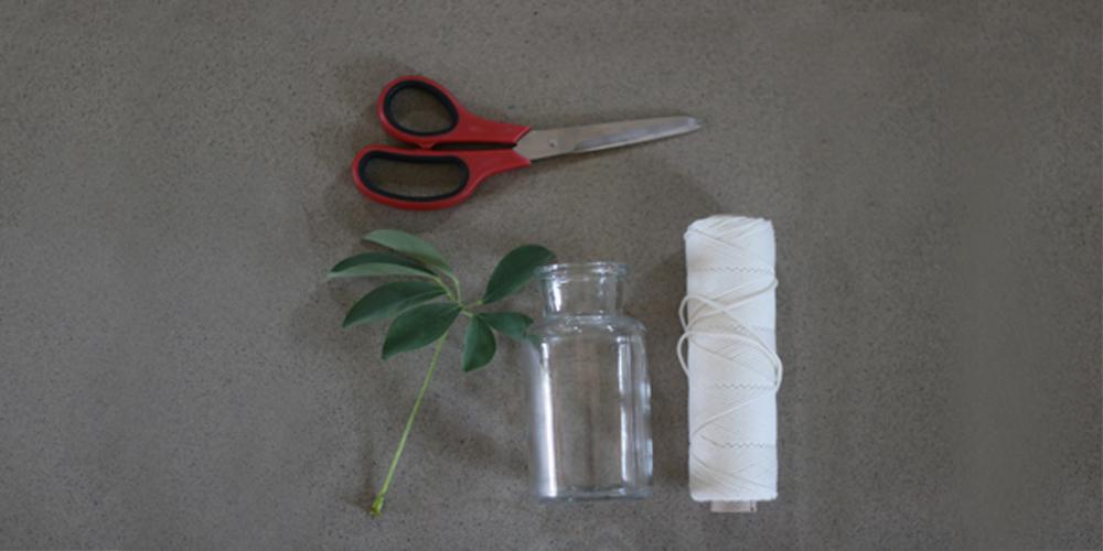 Du behöver ett garn att knyta med (det här är ett bomullsgarn, men ta vad du tycker är snyggast), en sax, något att knyta runt och kanske en liten blomma.