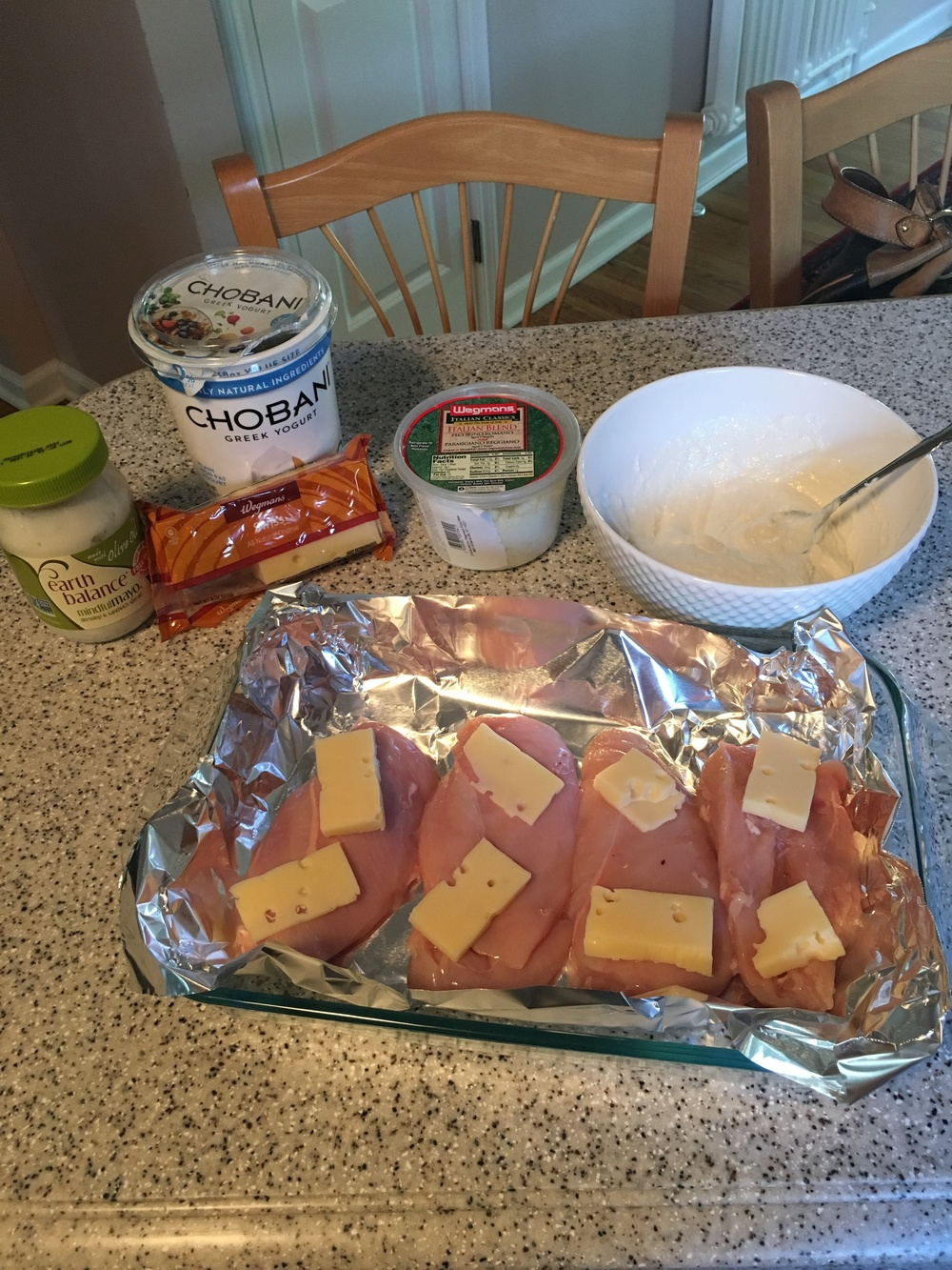 Ingredients shown above and slices of cheese on chicken in dish with foil