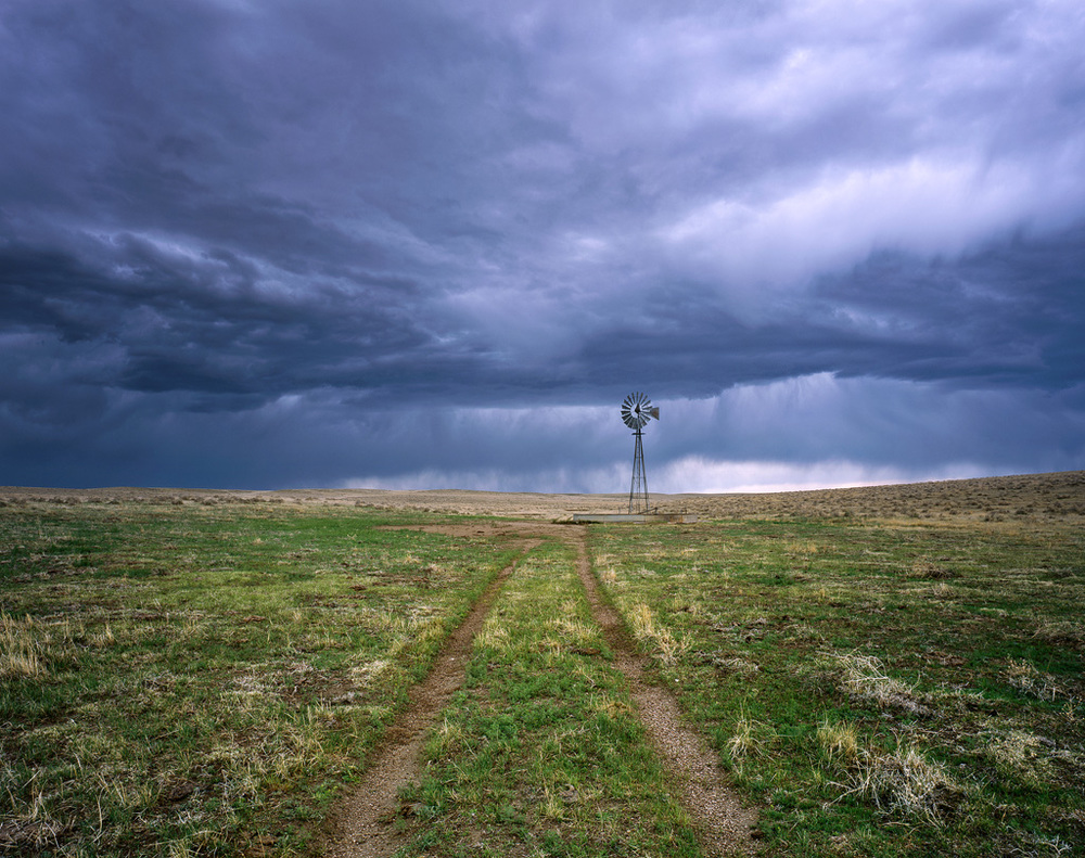 """Windmill, Two Track, Storm"" – I biked about 50 miles from home to spend the night on the Pawnee Grasslands, a bit of a May tradition for me.  Late in the afternoon the skies turned threatening and I had to seek shelter, but not before capturing this image during the calm before the storm.  Prints available."