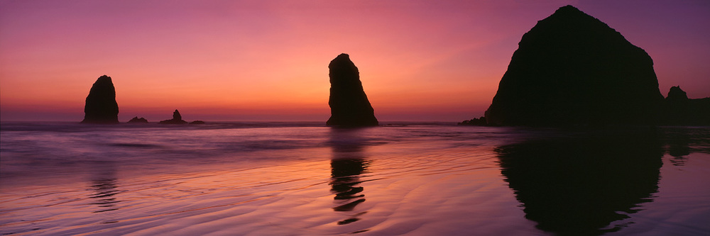 """Canon Beach Sunset"" – Sunset silhouettes over Haystack Butte and the other nearby seastacks.  Prints available."