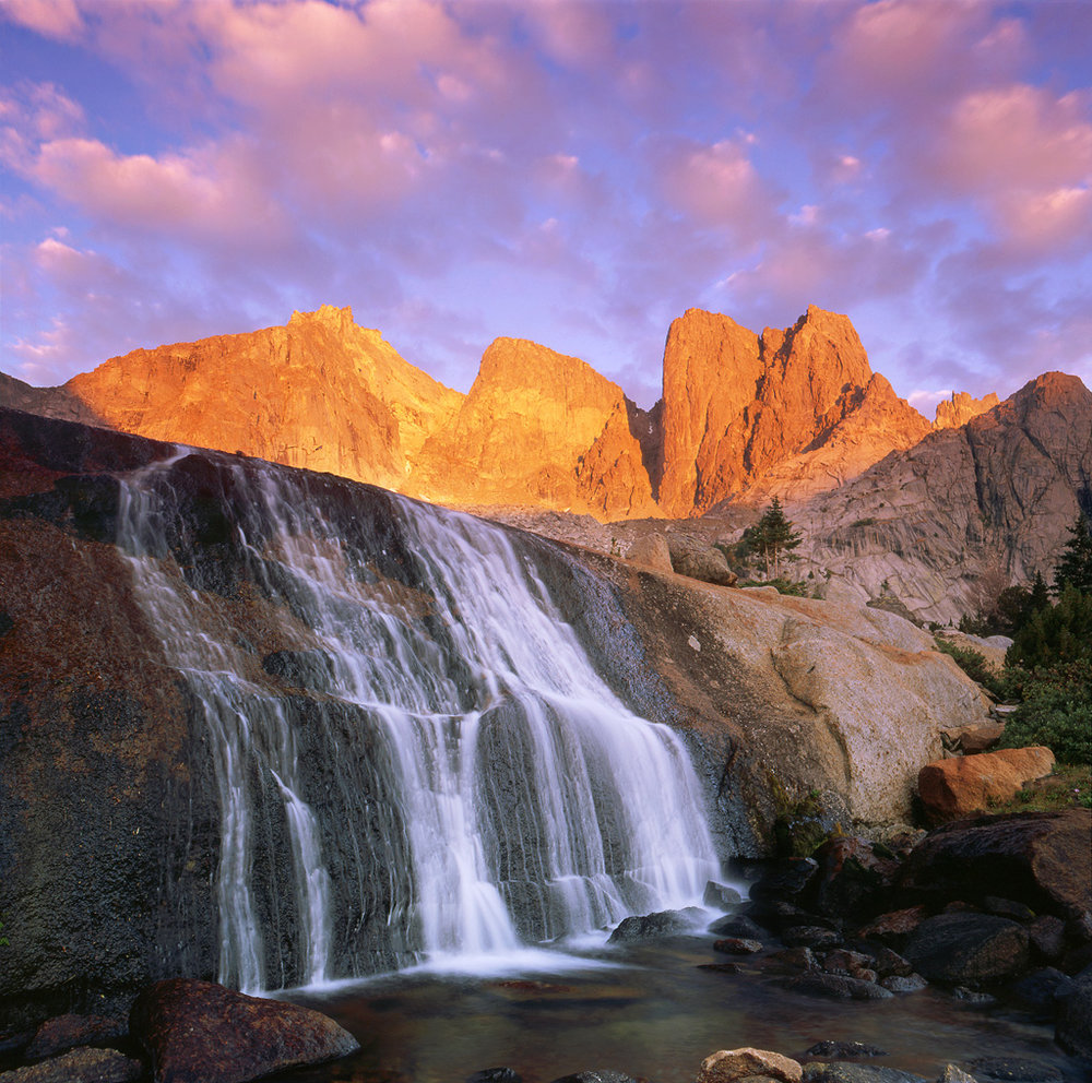"""Granite Flow"" - An epic sunrise over the Cirque of the Towers in the Wind River Range of Wyoming.  The unusual waterfall flows over a slab on granite in front of the rocky crags and peaks.  Prints Available."