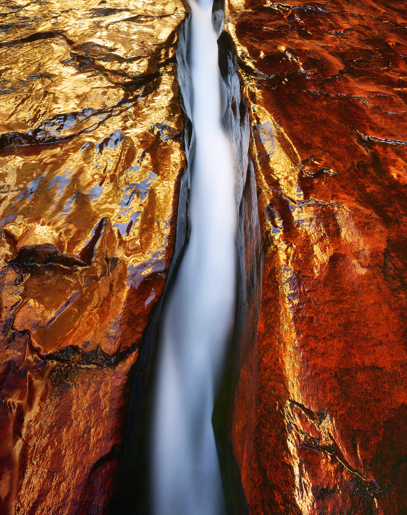 """Sandstone Flow"" - An entire creek rushes through a narrow crack in the deep red sandstone.  Sunlight reflected on a canyon wall makes the whole image glow brilliantly.  Prints Available."