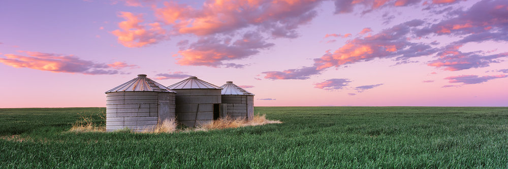 """Silos at Sunset"" - Silos stand in an endless field of wheat field below a vibrant sunset sky.  Prints available."