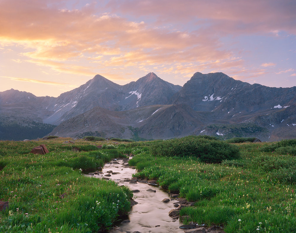 """""""Triple Peak Flow"""" - A midsummer backpacking trip brought me to this stunning view of an alpine stream meandering into looming peaks. The soft light of sunrise fills the valley with a warm glow.   Prints Available"""